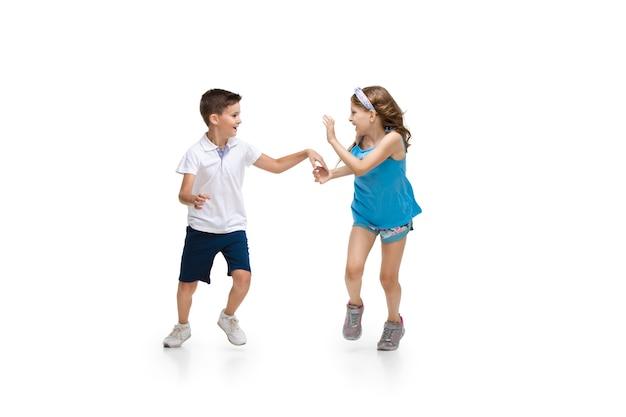 Niños felices, niño y niña caucásicos pequeños y emocionales saltando y corriendo aislado en blanco