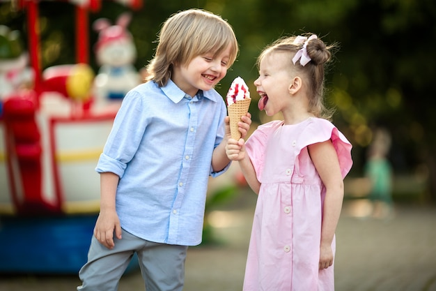 Niños felices, niño y niña comen helado en un parque de diversiones