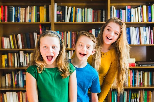 Niños felices de pie en la biblioteca