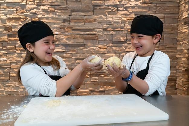 Niños felices y sonrientes sosteniendo una bola de masa en ropa de chef
