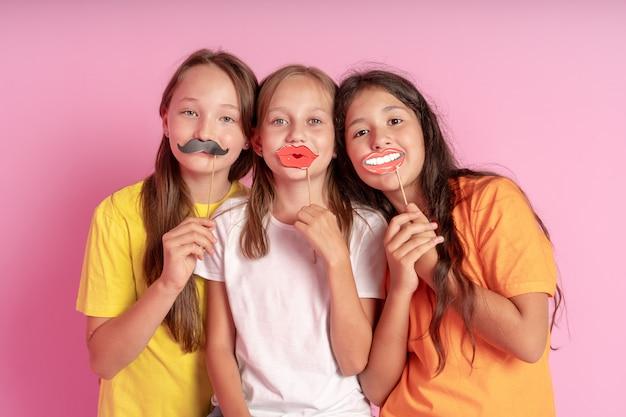Los niños felices tienen bigote falso y labios sobre un fondo rosa