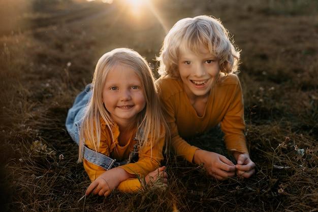 Niños felices de tiro completo sobre el césped