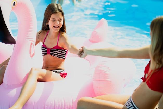 Niños felices tomados de la mano en la piscina