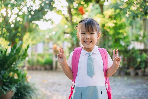 Niños felices en traje y bolsa de estudiante listos para ir a la escuela para aprender