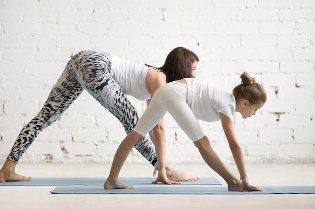 Niños de formación de maestros de yoga con un niño una parsvottanasana plantean