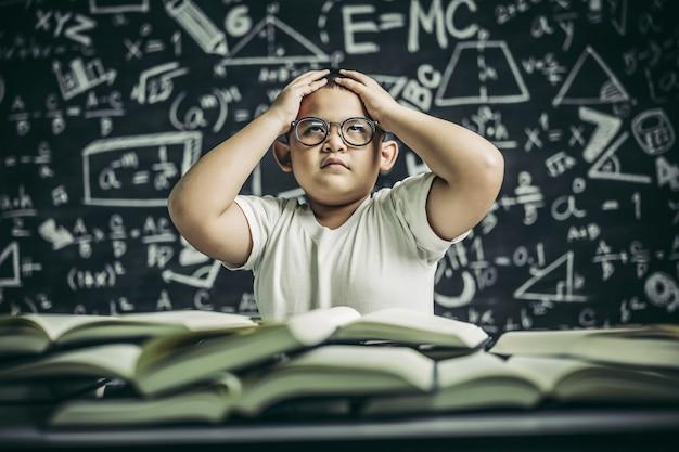 Los niños con gafas escriben libros y piensan en el aula.