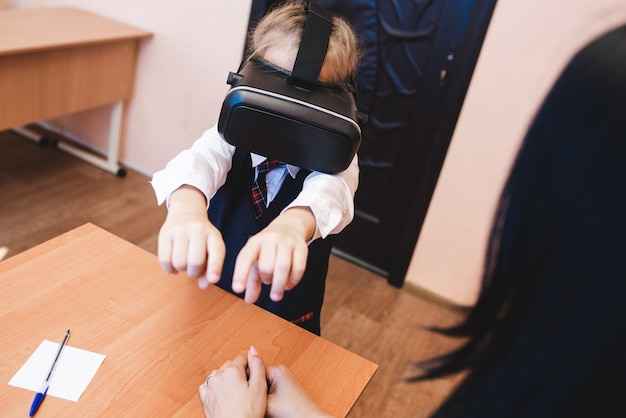 Los niños con gafas de realidad virtual están en la oficina de la escuela.