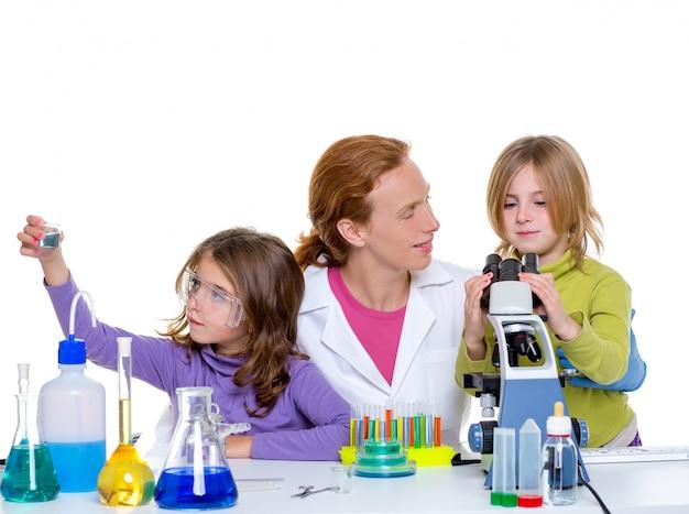 Niños girlas y maestra en laboratorio escolar