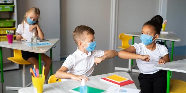 Niños golpeando el codo en clase