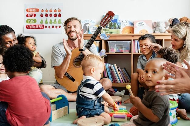 Niños de guardería tocando con instrumentos musicales en el aula.