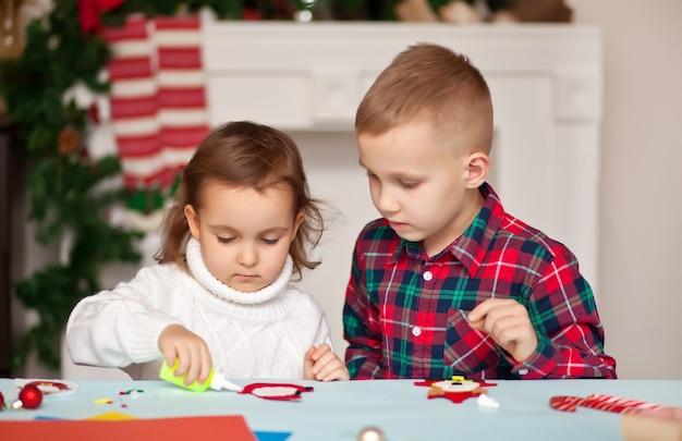 Niños haciendo decoración para árbol de navidad o regalos.