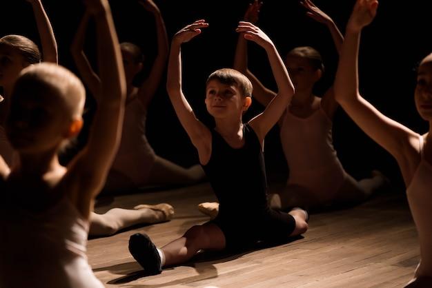 Niños haciendo divisiones mientras se calientan en el escenario