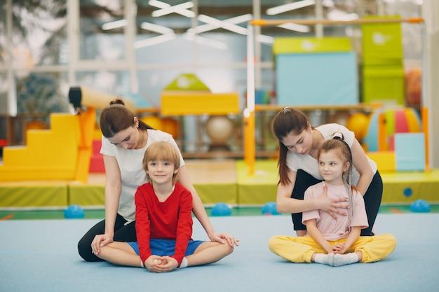 Niños haciendo ejercicios de estiramiento en el gimnasio en el jardín de infantes o la escuela primaria concepto de deporte y fitness para niños