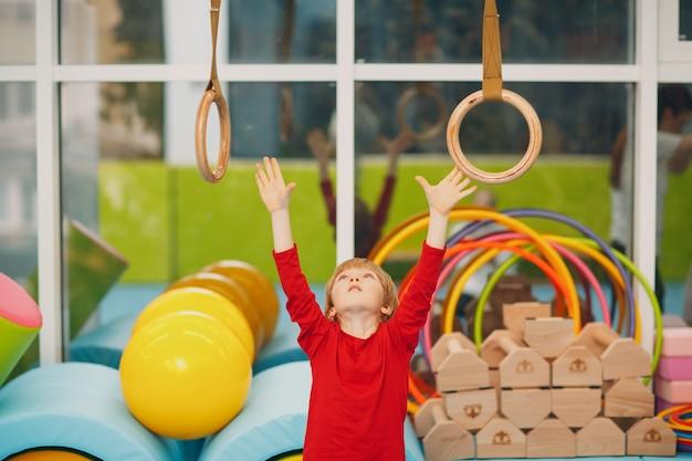 Niños haciendo ejercicios en el gimnasio en el jardín de infantes o en la escuela primaria concepto de anillos deportivos y deportivos para niños