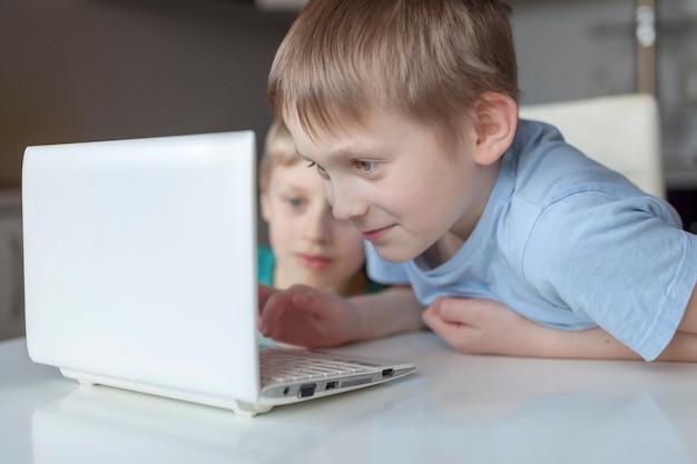Niños haciendo la tarea en casa. los muchachos miran la computadora portátil. de vuelta a la escuela. educación a distancia en línea educación