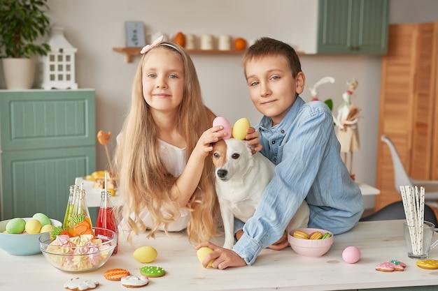 Niños con huevos de pascua en la cocina en un perro