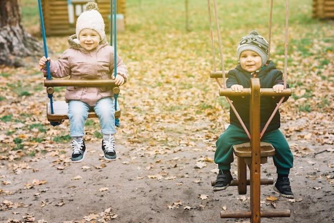 Niños iluminados por el sol columpiándose en el patio de otoño