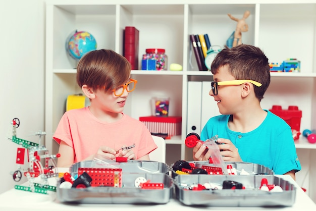 Niños inteligentes que crean construcciones de bricolaje en la mesa.