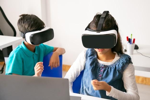 Niños irreconocibles jugando y usando auriculares vr