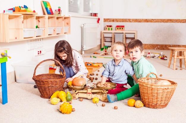 Niños en el jardín de infantes jugando y explorando el concepto de equilibrio usando pesas.