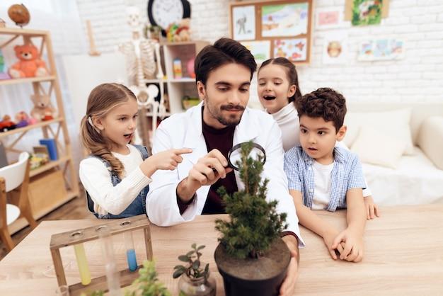 Los niños en el jardín de infantes miran bajo una lupa
