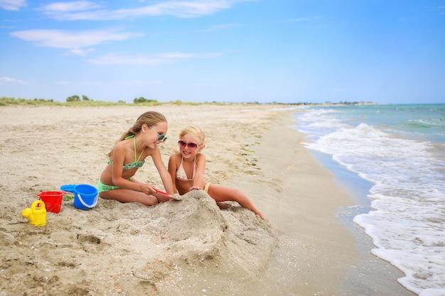 Los niños juegan con la arena en la playa.