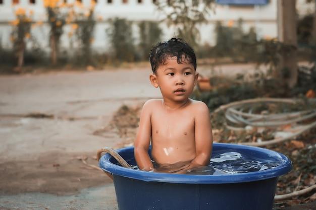 Los niños juegan y bañan agua en el jardín, sentados en un balde de agua.