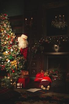 Los niños juegan cerca del árbol de navidad. el verdadero papá noel los está mirando.