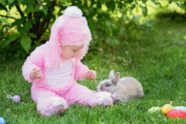 Los niños juegan con conejo de verdad. niño riendo en búsqueda de huevos de pascua con conejito mascota.