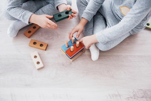 Los niños juegan con un diseñador de juguetes en el piso de la habitación de los niños. dos niños jugando con bloques de colores. juegos educativos de jardín de infantes