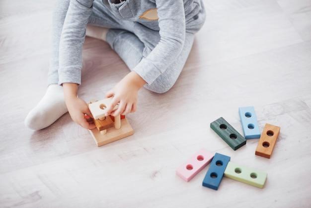Los niños juegan con un diseñador de juguetes en el piso de la habitación de los niños.
