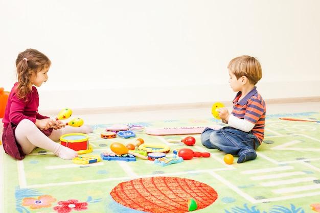 Los niños juegan con instrumentos musicales en el suelo.