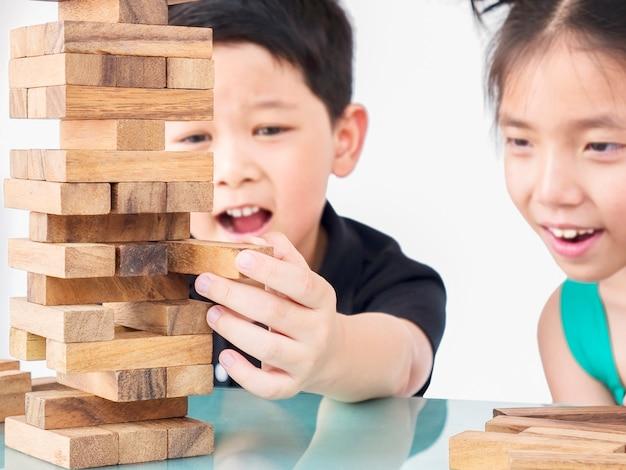 Los niños juegan jenga, un juego de torre de bloques de madera.