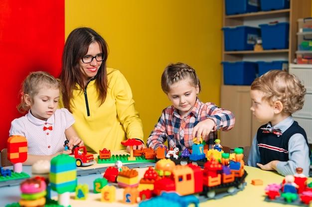 Niños jugando con bloques constructores en clase.