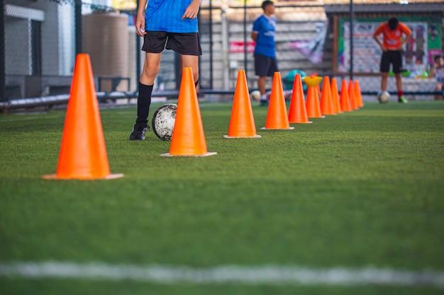 Niños jugando cono de tácticas de balón de fútbol de control en campo de hierba con antecedentes de formación formación de niños en fútbol