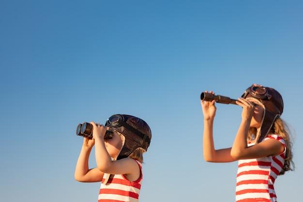 Niños jugando contra el fondo del cielo de verano. niños divirtiéndose al aire libre.