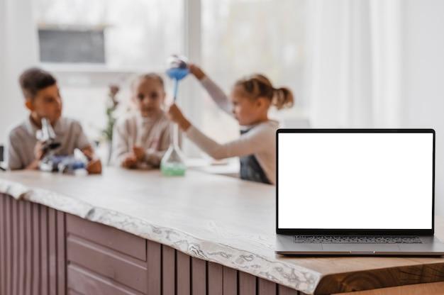 Niños jugando con elementos de química junto a una computadora portátil con pantalla en blanco