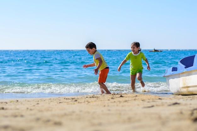 Niños jugando en la orilla del mar bajo la luz del sol