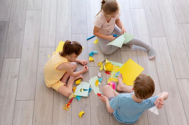 Niños jugando con papel full shot.