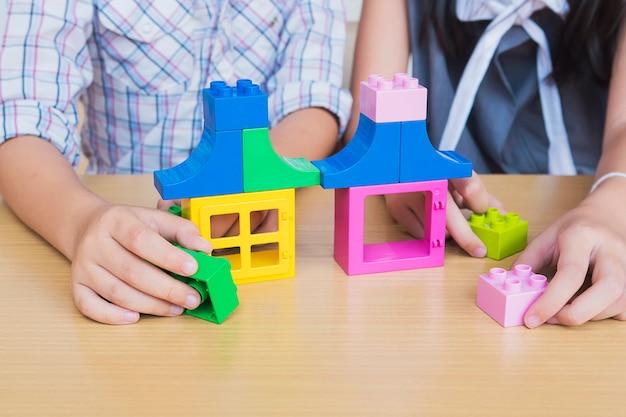 Niños jugando piezas de plástico de construcción creativa.