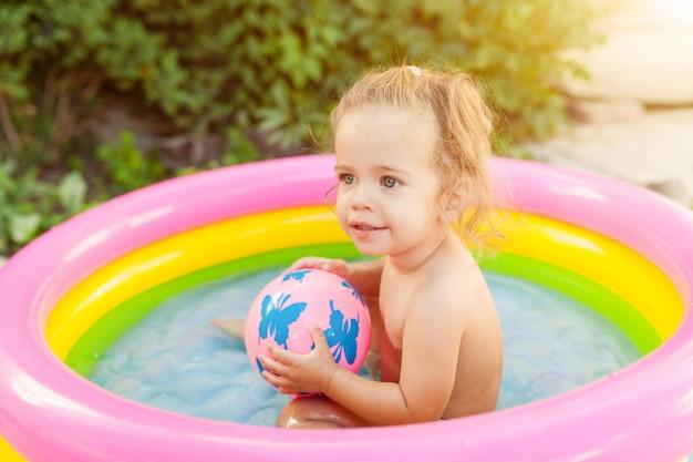 Niños jugando en la piscina inflable para bebés.