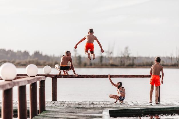 Niños jugando y saltando al agua en traje de baño.