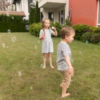 Niños jugando con soplador de burbujas