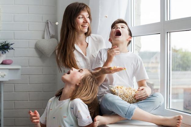 Niños juguetones comiendo palomitas de maíz con su madre en casa.