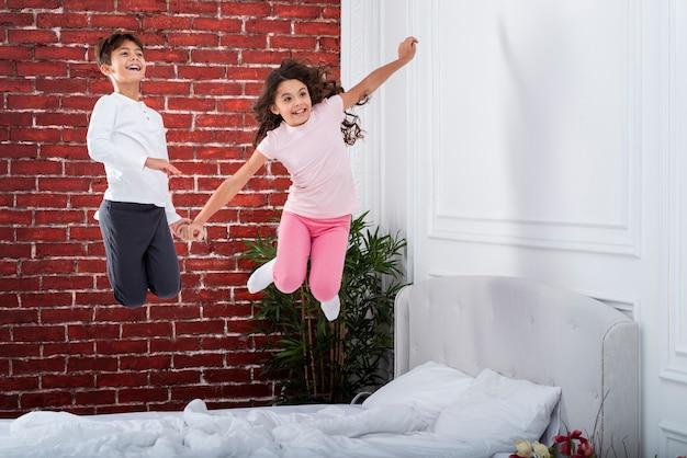 Niños juguetones saltando en la cama
