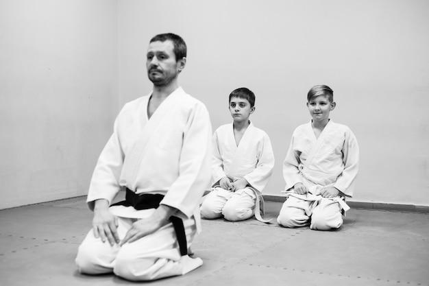 Los niños en kimono comienzan a entrenar en aikido.