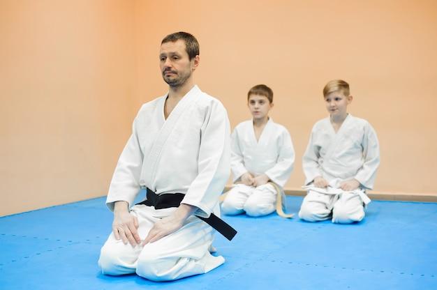 Los niños en kimono se sientan en el tatami con un entrenador en un seminario sobre artes marciales
