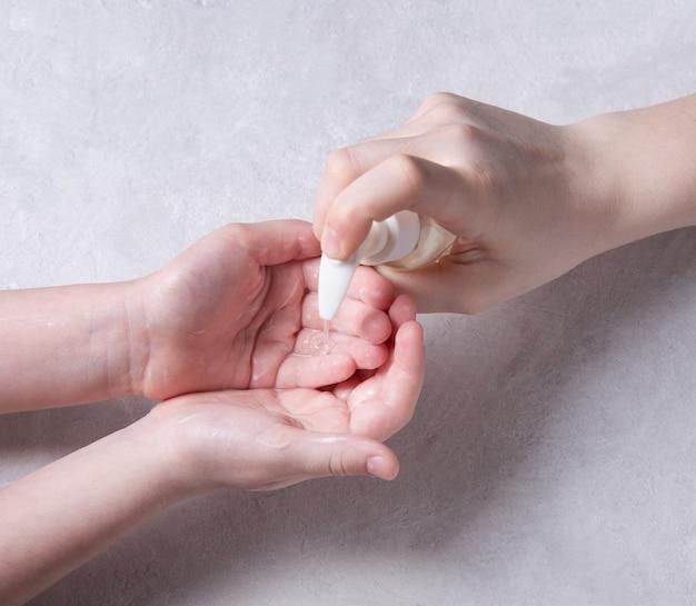 Los niños se lavan las manos con gel antibacteriano durante la pandemia de coronavirus