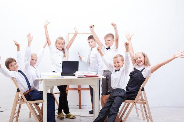 Niños levantando las manos sabiendo la respuesta a la pregunta
