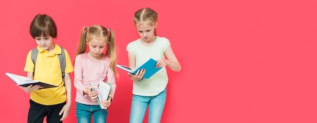 Niños leyendo algunos libros con espacio de copia.
